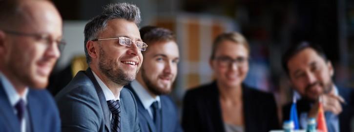 Geschäftsleute sitzen um einen Tisch bei einer Konferenz
