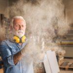 Handwerker entfernt Holzstaub: Eine wichtige Maßnahme, um Staubexplosionen vorzubeugen.