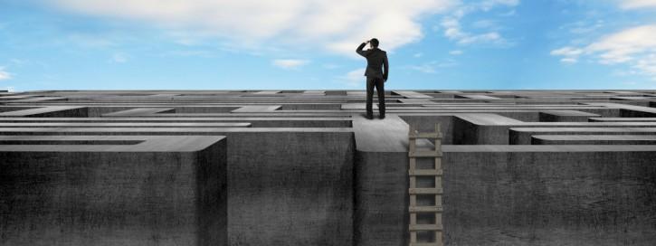 Mann neben einer Leiter auf einem Layrinth, über das er hinwegblickt