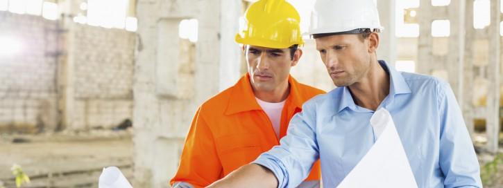 Architekt diskutiert mit Arbeiter über eine Blauzeichnung