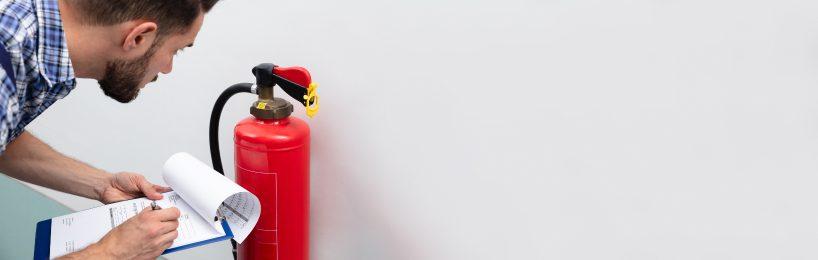 Brandschutzbeauftragter überprüft einen Feuerlöscher - eine seiner Aufgaben