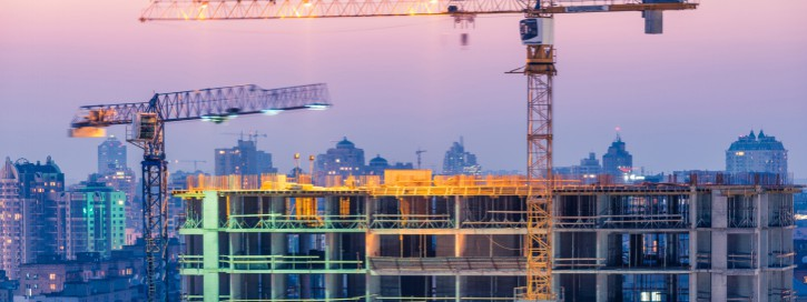 Construction of office building on purple sunset with two cranes