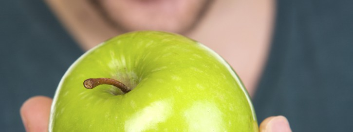 Mouth open and green organic apple