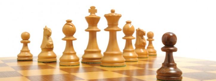 Schwarzer Bauer steht weißen Schachfiguren gegenüber