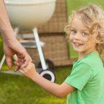 Lächelndes Kind hällt Vaters Hand