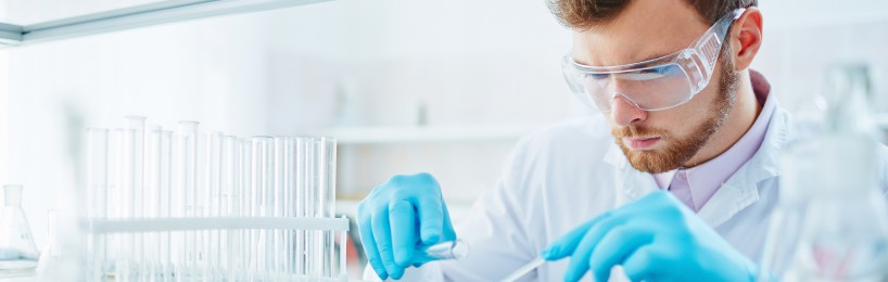 Mann arbeitet mit Gefahrstoffen im Labor - hier müssen die Gefährdungen beurteilt werden und er braucht eine Gefahrstoffunterweisung.