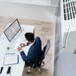 Blick von Klimaanlage hinunter auf den Arbeitsplatz: Falsches Lüften kann krank machen