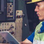 Mann prüft eine Maschine anhand von einer Checkliste auf seinem Tablet im Rahmen der Arbeitsmittelprüfung.