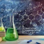 Chemikalien vor Tafel mit Chemie