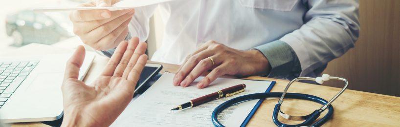 Ein Arzt gibt dem Arbeitgeber ein Attest oder eine Bescheinigung
