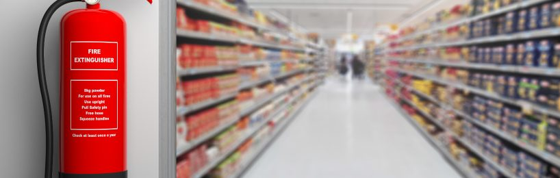 Feuerlöscher vor dem Korridor eines Supermarkts für wirksamen Brandschutz im Einzelhandel
