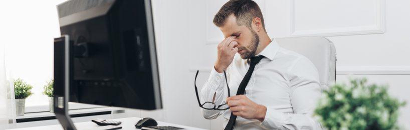 Mann reibst sich seine Augen, die vom Blick auf den Bildschirm müde geworden sind