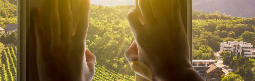 Hände vor geöffnetem Fenster beim Lüften