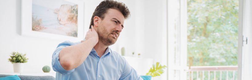 Junger Mann leidet an Nackenschmerzen: Nicht nur im Homeoffice kann fehlende Ergonomie und Bewegung die Gesundheit beeinträchtigen.