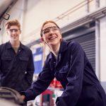 Zwei Praktikanten betrachten bei ihrem Schülerpraktikum einen Automotor.